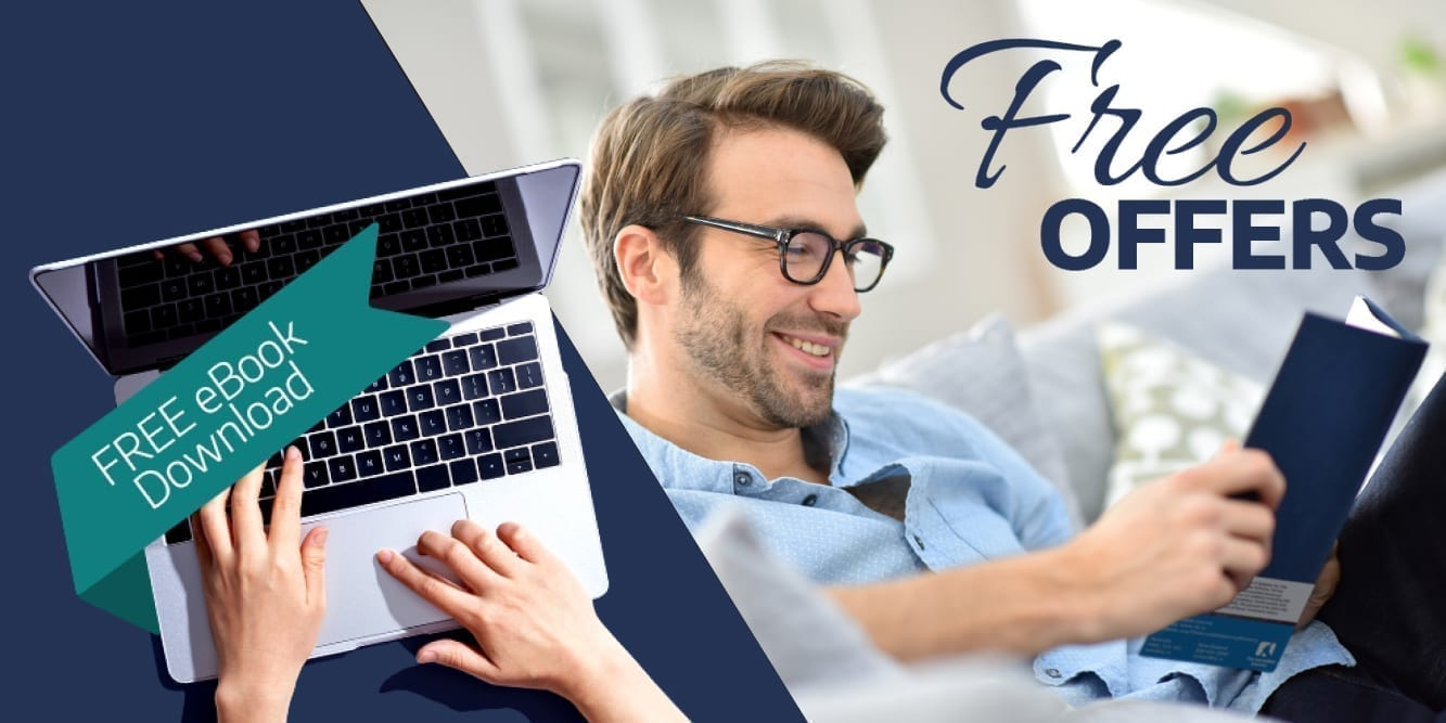 Man reading a book while opening the laptop